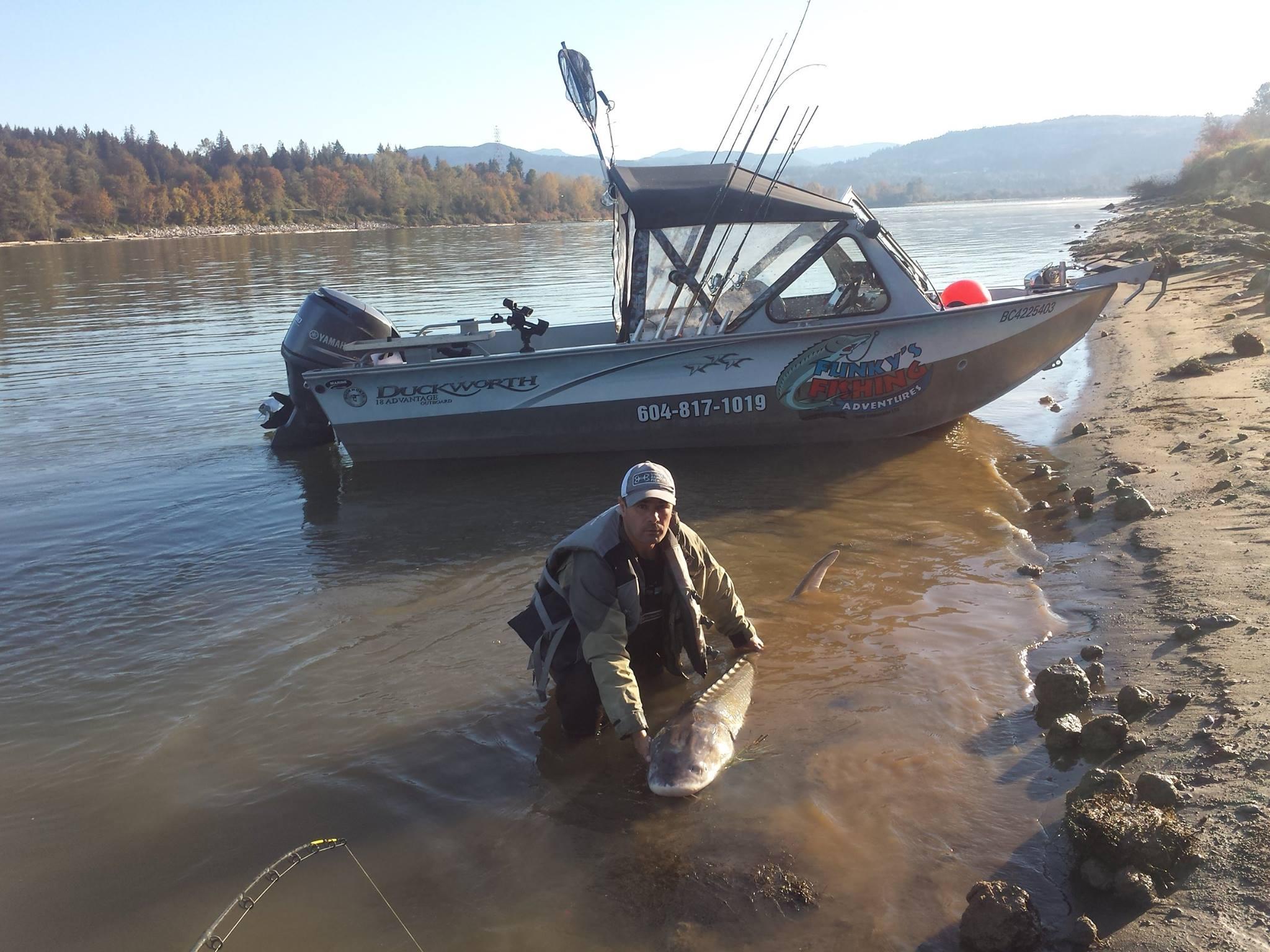 Rick Funk showing off a beautiful sturgeon fish he caught